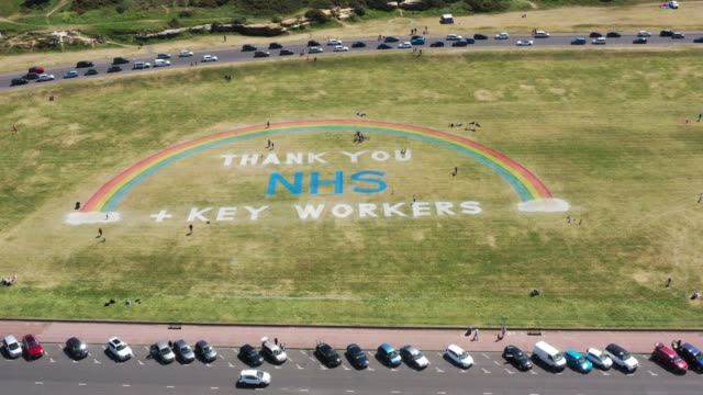 as the uk government ease lockdown restrictions people exercise and view a giant rainbow mural, created by wirral council, to thank nhs and key... - nhs bildbanksvideor och videomaterial från bakom kulisserna