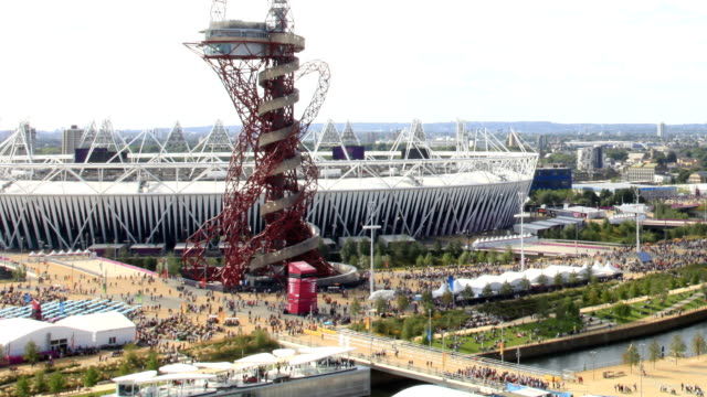 as this shot pulls out it reveals the london 2012 olympic park with all the crowds moving from one venue to another under a cloudy sky timelapse... - orbiting stock videos & royalty-free footage