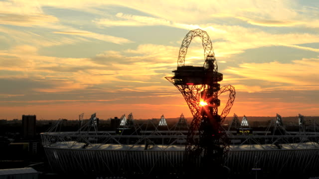 As this timelapse develops the sun passes behind the Mittal Orbit Tower and London 2012 Paralympic Stadium before dipping behind the horizon leaving...