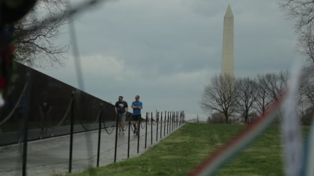 vídeos de stock, filmes e b-roll de as washington monument stands in the background ribbons on a wreath fly at vietnam veterans memorial at the national mall april 1 2020 in washington... - maryland estado