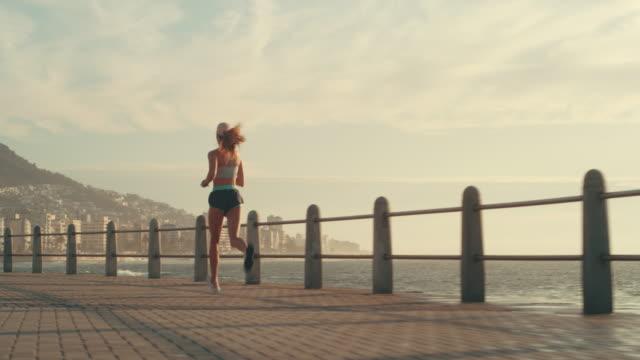 vídeos de stock e filmes b-roll de as we run, we become - atrás