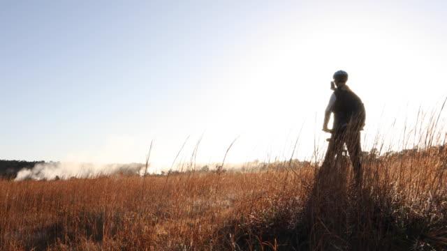 vídeos de stock, filmes e b-roll de dolly shot as woman bikes into meadow and watches sunrise over mist - smart