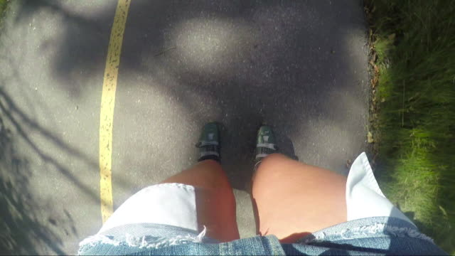 POV as young woman in-line skates on paved path