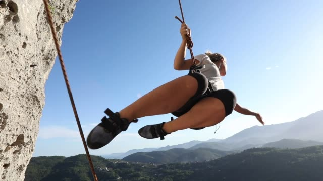 slo mo as young woman swings out from vertical rock face, while leading - scoperta video stock e b–roll