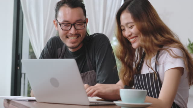 asain barista man and woman casual meeting with laptop about business plan in coffee shop - list stock videos & royalty-free footage