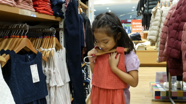 asain girl in purple t-shirt shopping dress in boutique store - garment stock videos & royalty-free footage