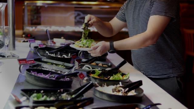 vidéos et rushes de asain homme client choisissant salade au bar à salade. - salade verte