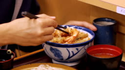 Asain Man eating a Japanese tempura on a bowl of rice