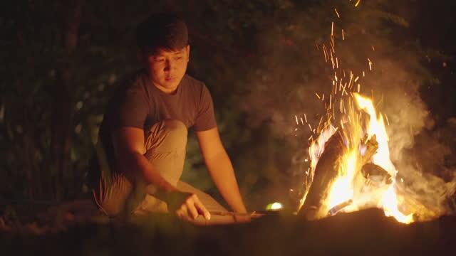 森の中でたき火を述べるアシンマン - 外乗点の映像素材/bロール