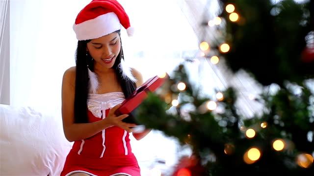 asain woman in santa hat opening gift box - santa hat stock videos & royalty-free footage