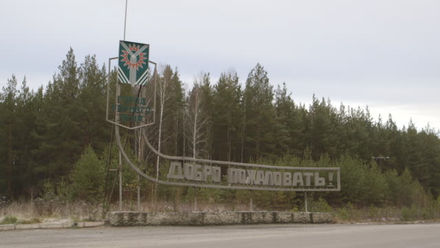 asbest town crest and welcome sign on road, wide shot - asbest stock-videos und b-roll-filmmaterial