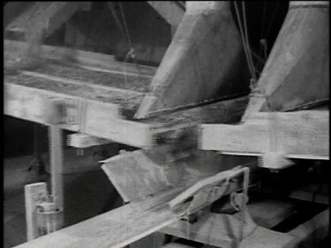 1921 MONTAGE Asbestos fibers passing over shaker screens then being lifted from serpentine rock by air suction on machine / Asbestos, Quebec, Canada