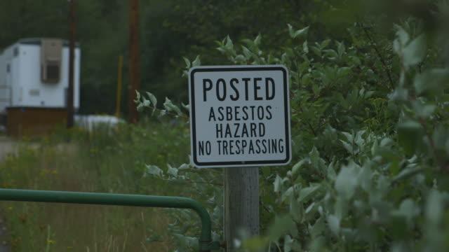 asbestos hazard sign, wide shot - asbest stock-videos und b-roll-filmmaterial