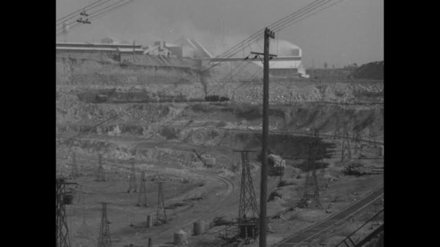 asbestos mine, with steam shovel in middle ground and train belching black smoke and hauling open rail cars in background / train pushes rail cars... - アスベスト点の映像素材/bロール