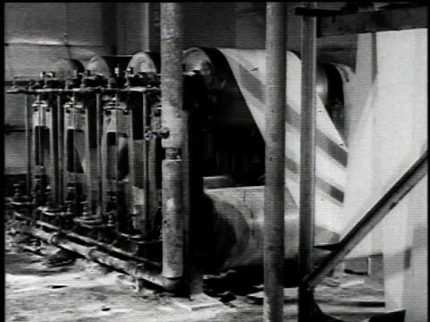 1921 montage asbestos paper mill, sheets of asbestos felt rolling through and being processed by various factory machines saturating them with asphalt / united states - アスベスト点の映像素材/bロール