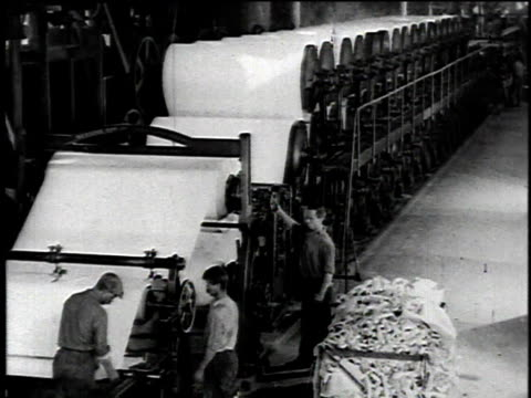 1921 montage asbestos paper mill, workers operating machines which dry and roll large reams of the paper / united states - アスベスト点の映像素材/bロール