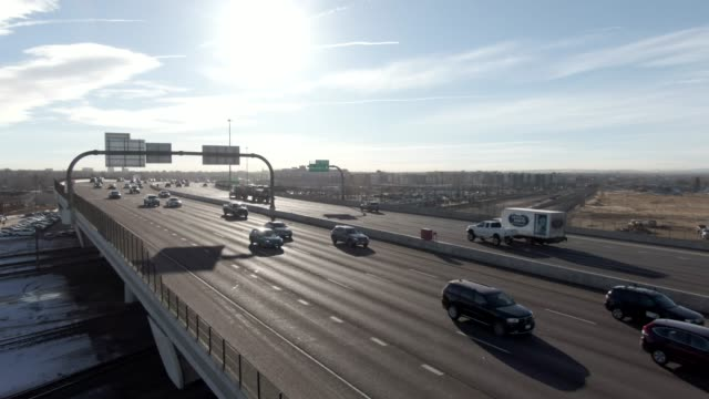 ascending aerial drone shot of a busy interstate 70 overpass in denver on a sunny morning - segnaletica stradale video stock e b–roll