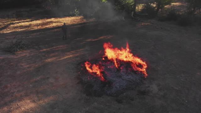 彼の 40 代をかき集めて棒と大きな炎を燃やす杭屋外に葉の男の昇順の空中ドローン ショット - 干草用熊手点の映像素材/bロール