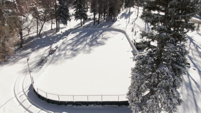 vídeos de stock e filmes b-roll de ascending aerial drone shot of a small outdoor snow-covered ice rink surrounded by snowy pine trees on a bright winter's day - pista de patinagem no gelo