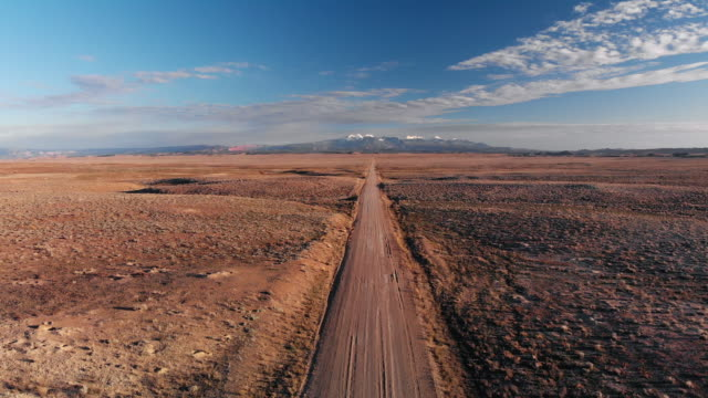 ascending aerial drone shot of a vanishing point dirt road with mountains in the background outside of moab, utah with desert plains on either side underneath a blue sky at sunset/sunrise - moab utah stock videos & royalty-free footage