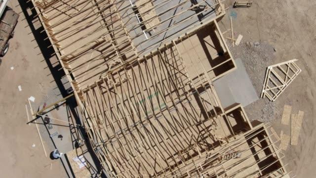 vídeos de stock, filmes e b-roll de drone aéreo ascendente disparado de trabalhadores da construção que andam através de uma casa estão moldando em um dia ensolarado - imperfeição