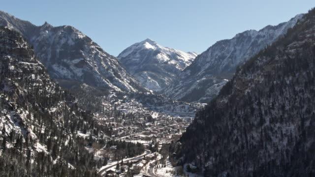 青空の下でコロラド州ユーレイの上の木の雪に覆われた森林とサンファン山脈 (ロッキー山脈) の雪のかぶった頂上の空中ドローン ショットを昇順 - ユアレイ市点の映像素材/bロール