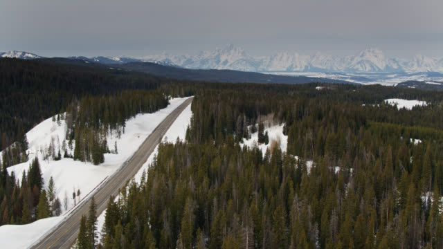 ascending aerial shot of road approaching grand teton national park in winter - grand teton stock videos & royalty-free footage