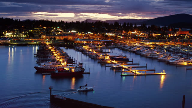 ascending aerial shot of small sailboat pulling in to anacortes marina at night - anacortes stock videos & royalty-free footage
