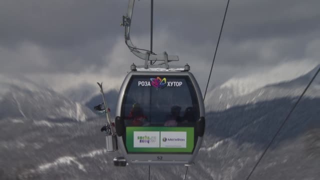 vídeos y material grabado en eventos de stock de ascending and descending cable cars viewed from below mountain range and clouds in background skiers on slope / low angle view cable cars sun shining... - sochi