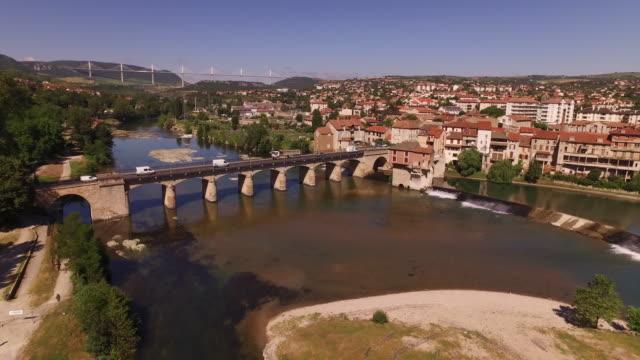 vidéos et rushes de ascending drone of millau including viaduct, old bridge and river tarn - au loin