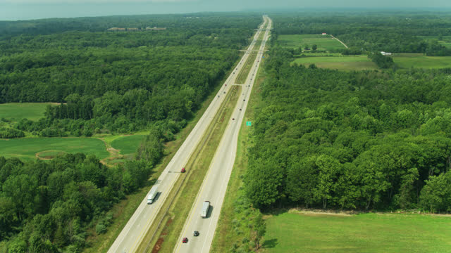ascending drone shot following truck leaving rest stop - michigan stock videos & royalty-free footage