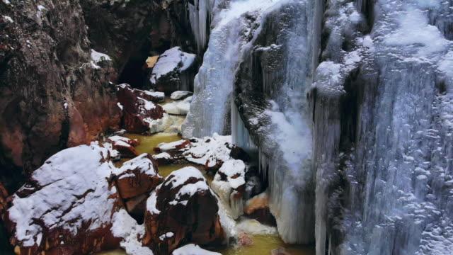 雪、ストリーム、コロラド州ユーレイでつらら (氷公園) の壁との狭い山渓谷のドローン ショットを昇順 - ユアレイ市点の映像素材/bロール