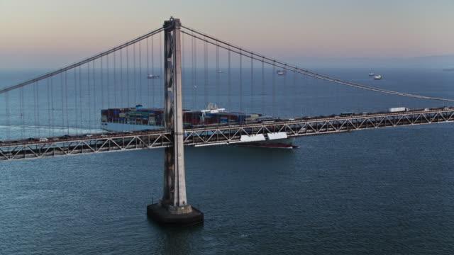 vidéos et rushes de coup de drone ascendante du navire cargo dans la baie de san francisco et le bay bridge - san francisco oakland bay bridge