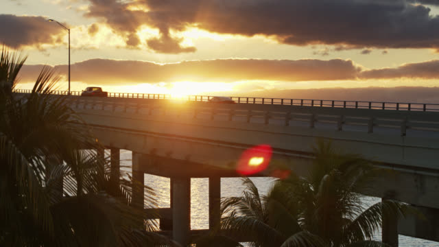 ascending drone shot of cars and cyclists on rickenbacker causeway at sunrise - biscayne bay stock videos & royalty-free footage