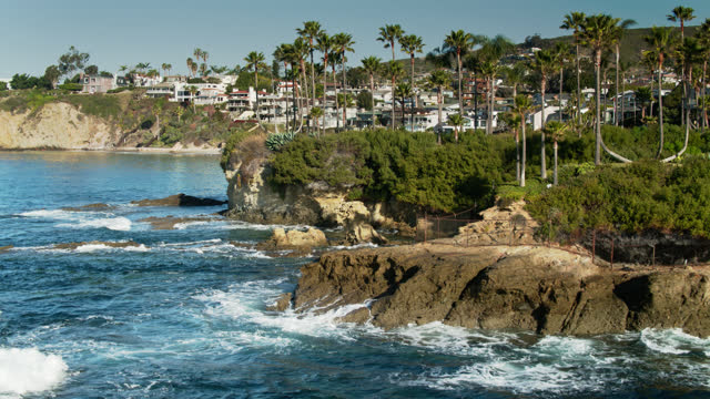 ascending drone shot of crashing waves, palm trees and clifftop houses in laguna beach - laguna beach california stock videos & royalty-free footage
