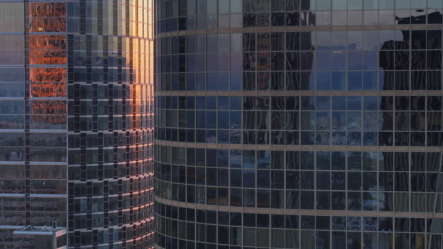 vídeos de stock e filmes b-roll de ascending drone shot of curved modern office towers at sunset - arranha céu