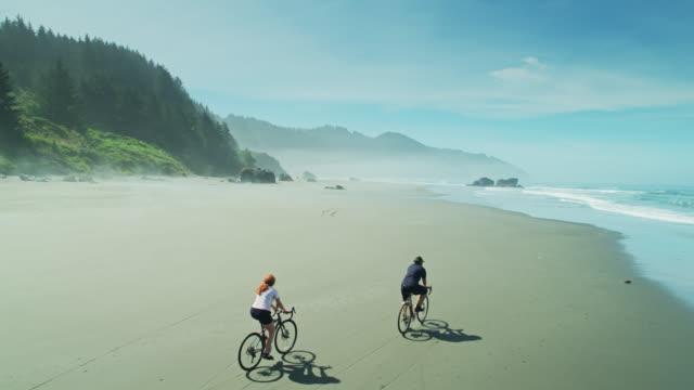 colpo di drone ascendente di ciclisti a whaleshead beach, oregon - oregon stato usa video stock e b–roll