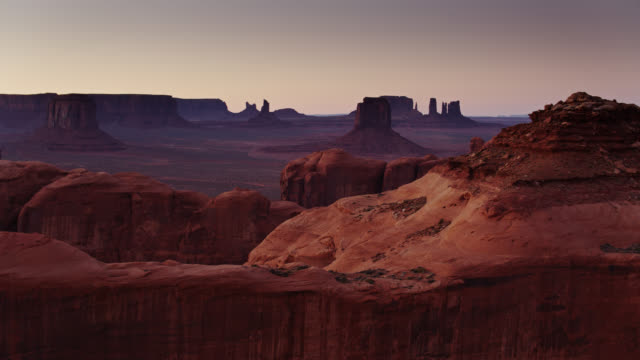 ascending drone shot of partially silhouetted buttes in monument valley from behind rocky outcrop - butte rocky outcrop stock videos & royalty-free footage