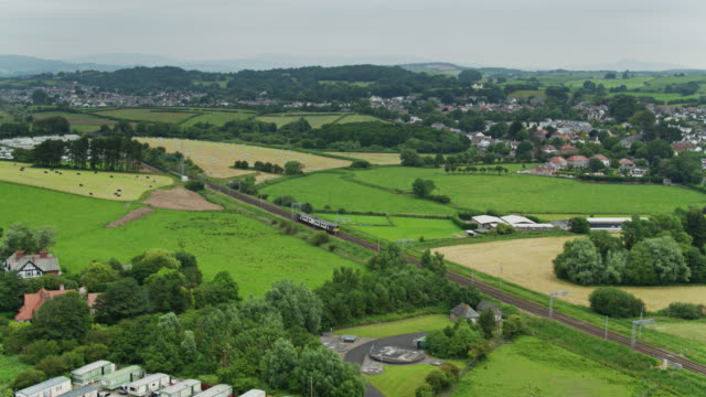ascending drone shot of passenger train crossing lancashire countryside - railroad track stock videos & royalty-free footage