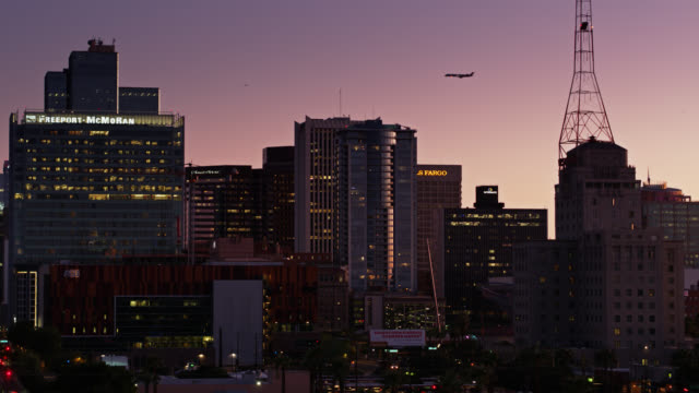 ascending drone shot of plane flying over phoenix at twilight - dusk stock videos & royalty-free footage