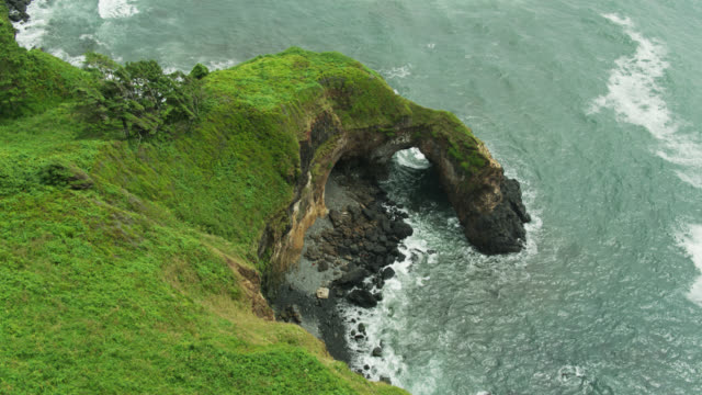 ascending drone shot of water flowing through natural stone arch on oregon coast - oregon coast stock videos & royalty-free footage