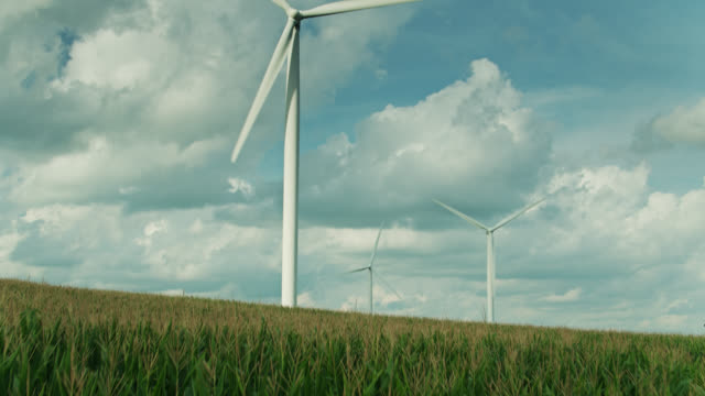 vídeos de stock e filmes b-roll de ascending drone shot of wind turbines in field of corn - environmental conservation
