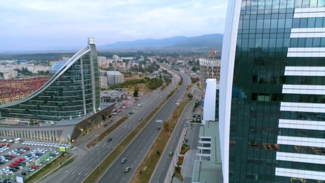 Ascending moving up drone shot of a big city highway revealing business buildings