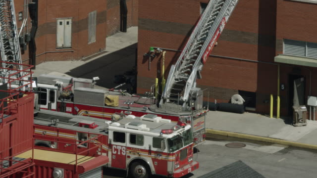 ascending shot from ladder trucks to firefighter trainees standing on a rooftop at the fire department of the city of new york training center - fire department of the city of new york stock videos and b-roll footage