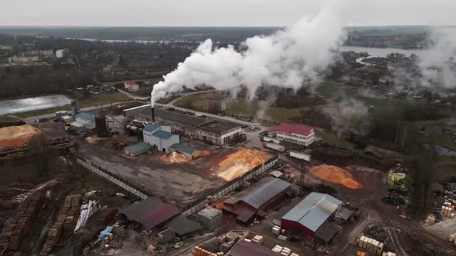 ascending shot of operating log sawmill factory with large chimney emitting smoke aerial - 材木置き場点の映像素材/bロール