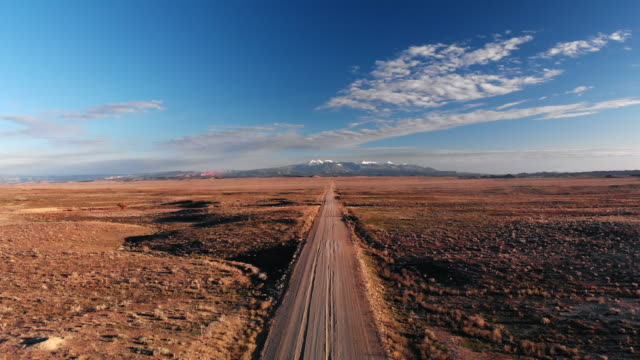 ascending trucking aerial drone shot of a vanishing point dirt road with mountains in the background outside of moab, utah with desert plains on either side underneath a blue sky at sunset/sunrise - strada in terra battuta video stock e b–roll