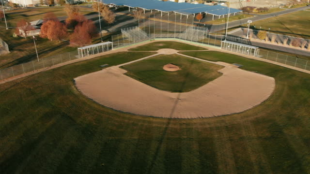 ascending trucking back aerial drone shot of an empty baseball diamond/field at sunset/sunrise on a sunny day - baseball diamond stock videos and b-roll footage