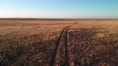 vídeos y material grabado en eventos de stock de ascendente camiones abejón aéreo delantero tiro de un par de pistas de neumático por un llano desierto en utah bajo un claro, azul cielo en la puesta de sol/amanecer - carretera de tierra