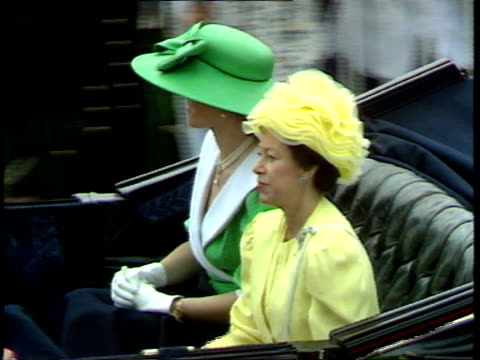 ENGLAND Berkshire Ascot Queen Mother wearing light blue outfit sits next Princess of Wales in turquoise widebrimmed hat large bow as along in open...