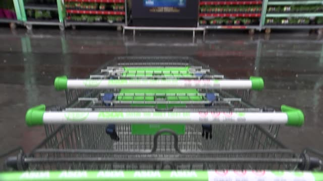 vídeos de stock e filmes b-roll de asda and sainsbury's general views england london clapham junction gvs asda supermarket / large banner on wall 'rolled back staying back' / stack of... - sainsburys